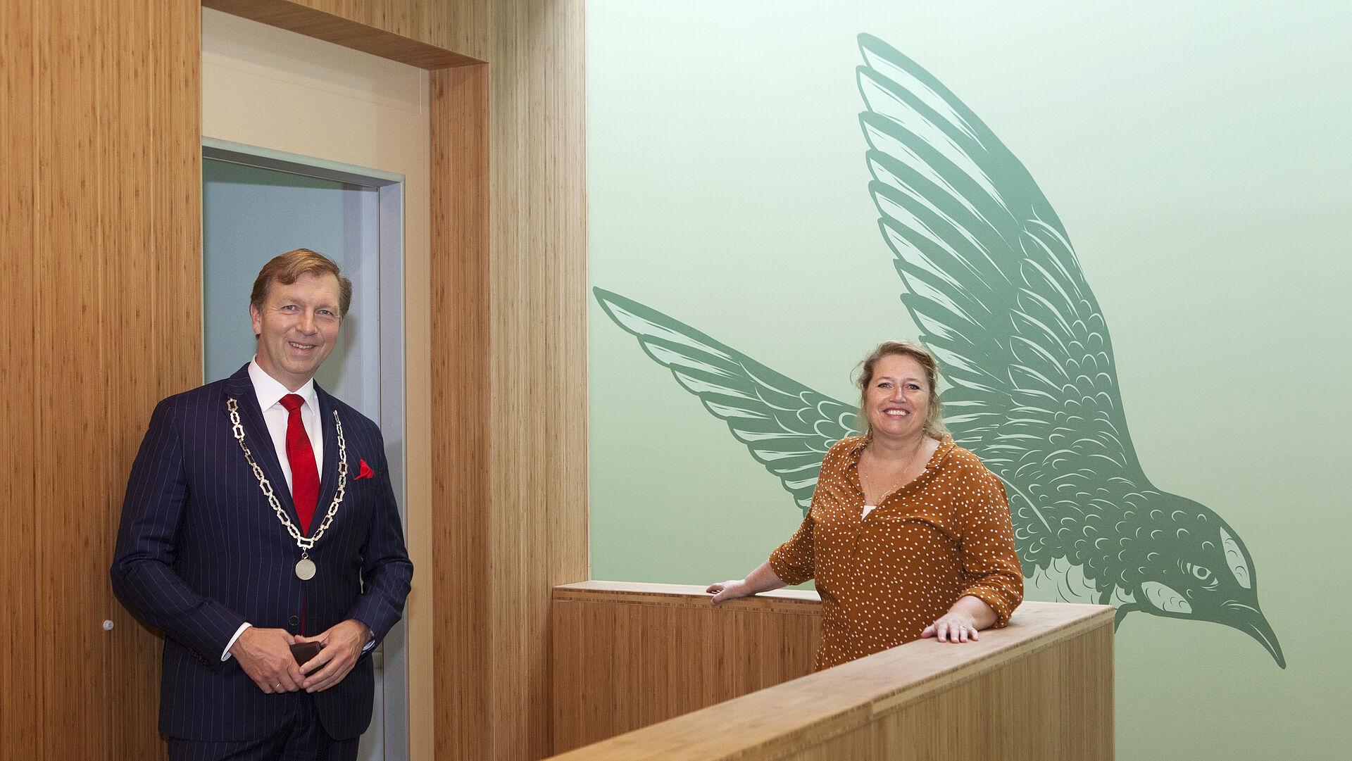Burgemeester en vrouw in het nieuwe IKC bij muurschildering zwaluw